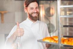 Een jonge knappe bakker toont zijn duim met een blad van verse croissants in zijn handen tegen de achtergrond van een oven royalty-vrije stock fotografie