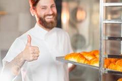 Een jonge knappe bakker toont zijn duim met een blad van verse croissants in zijn handen tegen de achtergrond van een oven royalty-vrije stock foto's