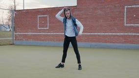 Een jonge, knappe, energieke kerel, een straatdanser in zwarte broek en een blauw bekleden met een kap uitvoerend acrobatisch stock videobeelden