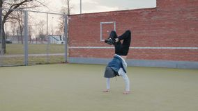 Een jonge, knappe, energieke kerel, een straatdanser in zwarte broek en een blauw bekleden met een kap, uitvoerend acrobatisch stock footage