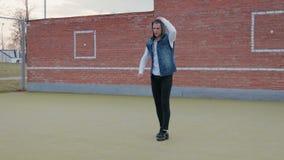 Een jonge, knappe, energieke kerel, een straatdanser in zwarte broek en een blauw vest met een kap, voert een acrobatische fles u stock footage