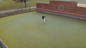 Een jonge, knappe, energieke kerel, een straatdanser in zwarte broeken en een witte sweater die een acrobatisch element uitvoeren stock footage