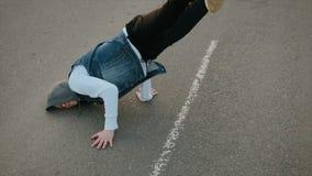Een jonge, knappe, energieke kerel in zwarte broek en een blauw vest die met een kap salto mortales uitvoeren en op de rijweg dan stock footage