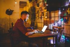 Een jonge knappe Kaukasische mens met baard en toothy glimlach in een rood geruit overhemd werkt achter een grijze laptop zitting stock fotografie