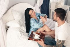 Een jonge, knappe jonge mens bracht croissants en koffie voor ontbijt in het bed aan zijn geliefd meisje stock fotografie