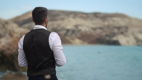 Een jonge knappe mens dichtbij het overzees en de bergen die stenen in het water werpen Langzame Motie cyprus Paphos stock video