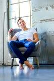 Een jonge knappe mens die in een leunstoel in een apar zolderstijl ontspannen stock afbeelding