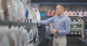 Een jonge knappe mens kiest een ijzer in een elektronikaopslag van de consument voor zijn nieuw huis Bestudeert de kenmerken stock footage