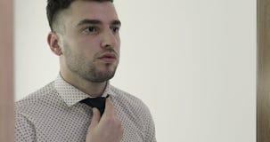 Een jonge knappe mens kleedt en past zijn band aan stock footage