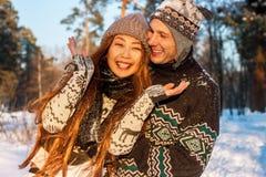 Een jonge knappe mens van Europese verschijning en een jong Aziatisch meisje in een park op de aard in de winter royalty-vrije stock afbeeldingen