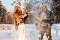 Een jonge knappe mens van Europese verschijning en een jong Aziatisch meisje in een park op de aard in de winter stock afbeelding