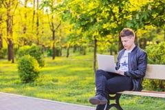 Een jonge knappe mens zit en werkt in het park met laptop De kerel freelancer werken buiten royalty-vrije stock foto