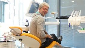 Een jonge knappe mensenzitting als tandartsenvoorzitter, draait hij, glimlacht in camera en toont een duim stock footage