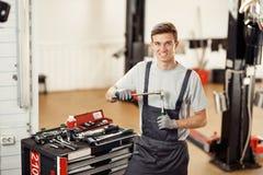 Een jonge knappe werktuigkundige is bij zijn werk terwijl het voorbereidingen treffen voor het herstellen van een auto royalty-vrije stock foto