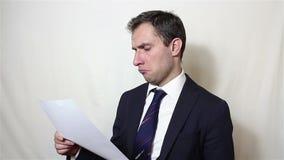 Een jonge knappe zakenman neemt een blad van document met een contract op en leest zorgvuldig het stock video