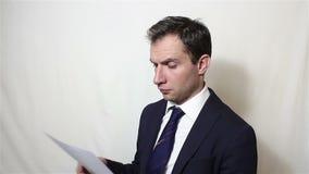 Een jonge knappe zakenman neemt een blad van document met een contract op en leest zorgvuldig het stock videobeelden
