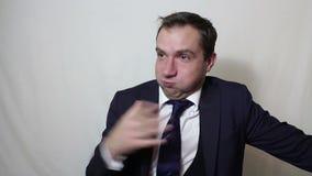 Een jonge knappe zakenman sluit zijn neus met zijn vingers voelend een stank stock footage