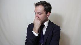 Een jonge knappe zakenman sluit zijn neus met zijn vingers voelend een stank stock video