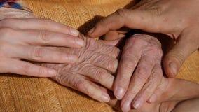 Een jonge man ` s en vrouwen` s handen die een oud paar handen van grootmoeder troosten openlucht stock videobeelden
