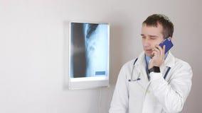 Een jonge mannelijke arts geeft een overleg telefonisch Witte muur en een Negatoscope met ribben en ribbenkast op de achtergrond stock videobeelden