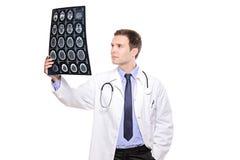 Een jonge medische arts die een CT aftasten analyseert stock fotografie