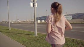 Een jonge meisjesjogging in de vroege ochtend Op de achtergrond, sportenfaciliteiten van het Olympische Park van Sotchi stock videobeelden