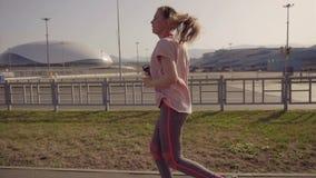 Een jonge meisjesjogging in de vroege ochtend Op de achtergrond, sportenfaciliteiten van het Olympische Park van Sotchi stock video