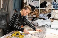 Een jonge meisjesontwerper van kleren De maatregelen door centimeter snijden lijn op de stof voor het maken van kleren Het maken  royalty-vrije stock foto