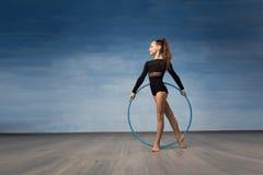 Een jonge meisjesturner in een zwart badpak kijkt in profiel in de handen van een gymnastiek- hoepel royalty-vrije stock foto
