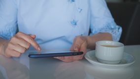 Een jonge meisjeszitting bij een lijst met een Kop van koffie, een digitale tablet in haar handen, die de catalogus van doorblade stock footage
