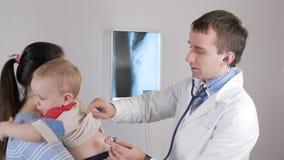 Een jonge mens arts controleert de baby` s longen Hij luistert erachter van de buik en van Babyglimlachen stock video