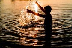 Een jonge mens baadt in het meer in de de zomertijd in de avond, het oranje spoor van de schroeiende zon Royalty-vrije Stock Fotografie