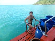 Een jonge mens beklimt aan boord van een overzees schip Stock Foto's