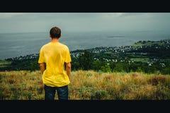 Een jonge mens bevindt zich met zijn rug tegen de achtergrond van het dorp royalty-vrije stock afbeeldingen