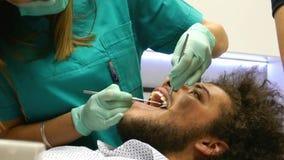Een jonge mens bij de tandarts, de tandarts controleert zijn tanden stock videobeelden