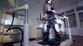Een jonge mens binnen een lagere lichaamsexoskeleton post stock footage