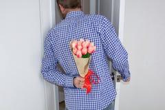 Een jonge mens in een blauw plaidoverhemd en jeans, die een boeket van tulpen achter zijn rug houden, en gluurt in de open deur stock foto's