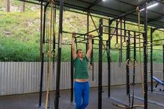 Een jonge mens in blauwe sportenbroek en een groene T-shirt voert ex uit stock foto