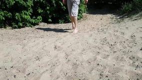 Een jonge mens in borrels loopt op het zand en het limping De ziekte is hersenverlamming Verlamming in volwassene stock videobeelden