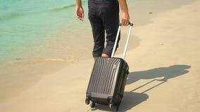Een jonge mens in broek en een klassiek overhemd met een koffer loopt langs het strand tegen de achtergrond van het turkooise ove stock fotografie