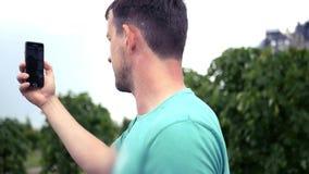 Een jonge mens communiceert telefonisch op een video van mededeling, toont de buurt van de stad HD, 1920x1080 langzaam stock video