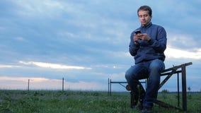 Een jonge mens controleert de berichten op de telefoon bij zonsondergang Een gebied van groen gras erachter Mooie hemel stock footage