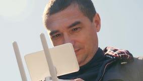 Een jonge mens controleert een hommel met afstandsbediening stock videobeelden