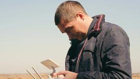 Een jonge mens controleert een hommel met afstandsbediening stock footage