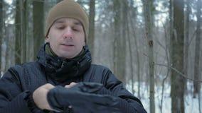 Een jonge mens in de winter bosvorst Hij ` s die op zijn handen ademen, wrijft en draagt een hoed en handschoenen Sneeuw en blauw stock videobeelden