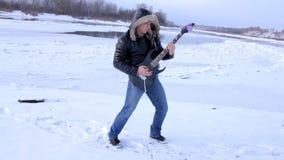 Een jonge mens in de winter om de gitaar te spelen stock footage