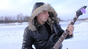Een jonge mens in de winter om de gitaar te spelen stock videobeelden