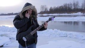 Een jonge mens in de winter om de gitaar te spelen stock video