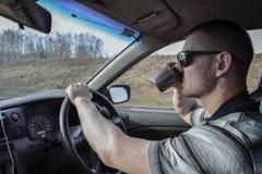 Een jonge mens die een auto het drinken koffie drijven Gevaarlijke situatie op de weg stock foto