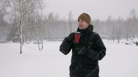 Een jonge mens die een hete drank van een thermosfles in een de winter bos Grote sneeuwval drinken De man onderzoekt de camera stock video